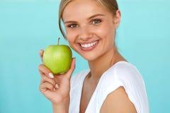 Χαμογελώντας γυναίκα με το όμορφο χαμόγελο, λευκιά εκμετάλλευση Apple δοντιών Στοκ Εικόνες
