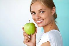 Χαμογελώντας γυναίκα με το όμορφο χαμόγελο, λευκιά εκμετάλλευση Apple δοντιών Στοκ εικόνες με δικαίωμα ελεύθερης χρήσης