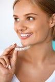 Χαμογελώντας γυναίκα με το όμορφο χαμόγελο που χρησιμοποιεί τα δόντια που λευκαίνουν το δίσκο στοκ φωτογραφία με δικαίωμα ελεύθερης χρήσης