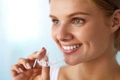 Χαμογελώντας γυναίκα με το όμορφο χαμόγελο που χρησιμοποιεί τον αόρατο εκπαιδευτή δοντιών Στοκ φωτογραφία με δικαίωμα ελεύθερης χρήσης
