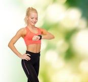 Χαμογελώντας γυναίκα με το όργανο ελέγχου ποσοστού καρδιών σε διαθεσιμότητα Στοκ εικόνες με δικαίωμα ελεύθερης χρήσης