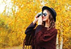 Χαμογελώντας γυναίκα μόδας φθινοπώρου με την αναδρομική εκλεκτής ποιότητας κάμερα που φορά τα γυαλιά ηλίου μαύρων καπέλων και πλε Στοκ φωτογραφία με δικαίωμα ελεύθερης χρήσης