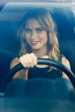 Χαμογελώντας γυναίκα πίσω από τη ρόδα του αυτοκινήτου, κάθετη σύνθεση Στοκ Φωτογραφία