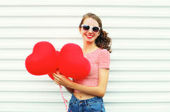 Χαμογελώντας γυναίκα πορτρέτου με τη μορφή καρδιών μπαλονιών αέρα που έχει τη διασκέδαση Στοκ φωτογραφία με δικαίωμα ελεύθερης χρήσης