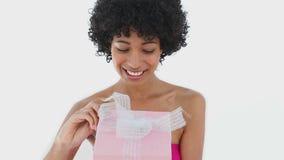 Χαμογελώντας γυναίκα που ανοίγει ένα κιβώτιο δώρων απόθεμα βίντεο