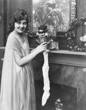 Χαμογελώντας γυναίκα που γεμίζει τη γυναικεία κάλτσα Χριστουγέννων (όλα τα πρόσωπα που απεικονίζονται δεν ζουν περισσότερο και κα Στοκ εικόνες με δικαίωμα ελεύθερης χρήσης