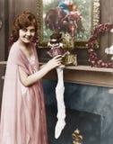 Χαμογελώντας γυναίκα που γεμίζει τη γυναικεία κάλτσα Χριστουγέννων (όλα τα πρόσωπα που απεικονίζονται δεν ζουν περισσότερο και κα Στοκ φωτογραφία με δικαίωμα ελεύθερης χρήσης