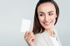Χαμογελώντας γυναίκα που εξετάζει την πιστωτική κάρτα υπό εξέταση στοκ φωτογραφία
