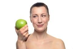 Χαμογελώντας γυναίκα που εξετάζει την πράσινη Apple σε ετοιμότητα της Στοκ Εικόνες