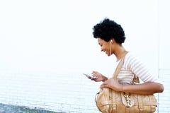 Χαμογελώντας γυναίκα που εξετάζει το playlist στο κινητό τηλέφωνο Στοκ Εικόνες