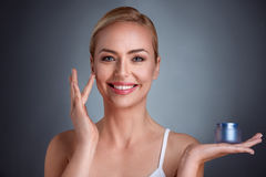 Χαμογελώντας γυναίκα που εφαρμόζει την κρέμα στο πρόσωπο Στοκ Φωτογραφία