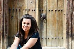 Χαμογελώντας γυναίκα που κάθεται μπροστά από την αρχαία πόρτα Στοκ φωτογραφία με δικαίωμα ελεύθερης χρήσης
