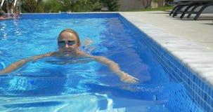Χαμογελώντας γυναίκα που κολυμπά στην εγχώρια λίμνη απόθεμα βίντεο