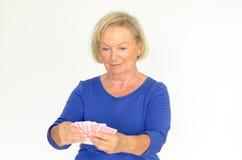 Χαμογελώντας γυναίκα που κρατά ένα χέρι των καρτών παιχνιδιού στοκ εικόνες