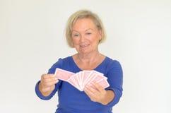 Χαμογελώντας γυναίκα που κρατά ένα χέρι των καρτών παιχνιδιού στοκ φωτογραφία