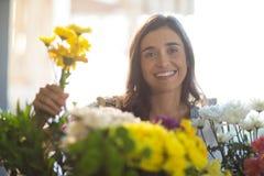 Χαμογελώντας γυναίκα που κρατά μια δέσμη των λουλουδιών στο κατάστημα ανθοκόμων Στοκ Εικόνες