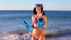 Χαμογελώντας γυναίκα που κρατά τα κολυμπώντας πτερύγιά της απόθεμα βίντεο