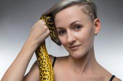 Χαμογελώντας γυναίκα που κρατά το κίτρινο φίδι Στοκ Εικόνες