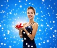 Χαμογελώντας γυναίκα που κρατά το κόκκινο κιβώτιο δώρων Στοκ Εικόνες