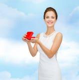 Χαμογελώντας γυναίκα που κρατά το κόκκινο κιβώτιο δώρων Στοκ Φωτογραφίες