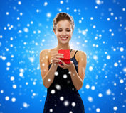 Χαμογελώντας γυναίκα που κρατά το κόκκινο κιβώτιο δώρων Στοκ Εικόνα