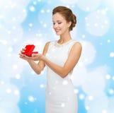 Χαμογελώντας γυναίκα που κρατά το κόκκινο κιβώτιο δώρων Στοκ εικόνες με δικαίωμα ελεύθερης χρήσης