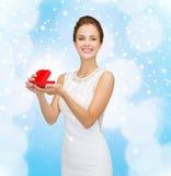 Χαμογελώντας γυναίκα που κρατά το κόκκινο κιβώτιο δώρων Στοκ φωτογραφία με δικαίωμα ελεύθερης χρήσης