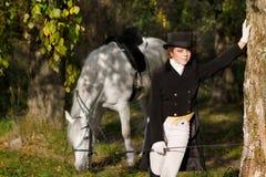 Χαμογελώντας γυναίκα που μένει κοντά στο άσπρο άλογο στοκ εικόνες με δικαίωμα ελεύθερης χρήσης
