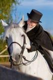 Χαμογελώντας γυναίκα που οδηγά σε ένα άσπρο άλογο στοκ εικόνες