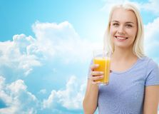 Χαμογελώντας γυναίκα που πίνει το χυμό από πορτοκάλι πέρα από τον ουρανό Στοκ Εικόνες