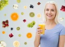 Χαμογελώντας γυναίκα που πίνει το χυμό από πορτοκάλι στο σπίτι Στοκ φωτογραφίες με δικαίωμα ελεύθερης χρήσης