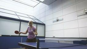 Χαμογελώντας γυναίκα που παίζει masterfully την αντισφαίριση στο δικαστήριο σε σε αργή κίνηση φιλμ μικρού μήκους
