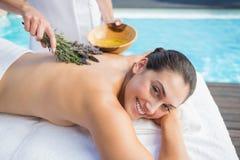 Χαμογελώντας γυναίκα που παίρνει ένα aromatherapy poolside επεξεργασίας Στοκ Εικόνες