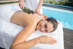 Χαμογελώντας γυναίκα που παίρνει ένα aromatherapy poolside επεξεργασίας Στοκ φωτογραφία με δικαίωμα ελεύθερης χρήσης