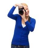 Χαμογελώντας γυναίκα που παίρνει την εικόνα με τη ψηφιακή κάμερα Στοκ εικόνες με δικαίωμα ελεύθερης χρήσης