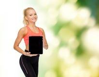 Χαμογελώντας γυναίκα που παρουσιάζει στο PC ταμπλετών κενή οθόνη Στοκ Εικόνες
