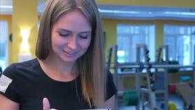 Χαμογελώντας γυναίκα που τρέχει treadmill που χρησιμοποιεί την ταμπλέτα φιλμ μικρού μήκους