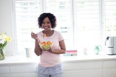 Χαμογελώντας γυναίκα που τρώει τη σαλάτα στην κουζίνα Στοκ εικόνες με δικαίωμα ελεύθερης χρήσης