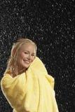 Χαμογελώντας γυναίκα που τυλίγεται στην πετσέτα στη βροχή Στοκ Εικόνες