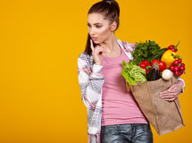 Χαμογελώντας γυναίκα που φέρνει μια τσάντα με τα λαχανικά Στοκ φωτογραφία με δικαίωμα ελεύθερης χρήσης