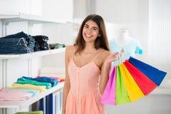 Χαμογελώντας γυναίκα που φέρνει τις ζωηρόχρωμες τσάντες αγορών στο κατάστημα ιματισμού στοκ φωτογραφία