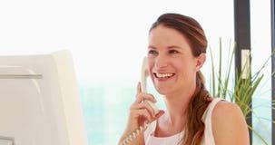 Χαμογελώντας γυναίκα που χρησιμοποιεί τον υπολογιστή ενώ έχοντας ένα τηλεφώνημα απόθεμα βίντεο