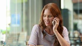 Χαμογελώντας γυναίκα που χρησιμοποιεί το smartphone και την κατοχή του τηλεφωνήματος φιλμ μικρού μήκους