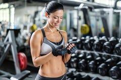 Χαμογελώντας γυναίκα που χρησιμοποιεί Smartphone στη γυμναστική Στοκ Εικόνες
