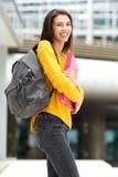 Χαμογελώντας γυναίκα σπουδαστής που περπατά στην κατηγορία με την τσάντα και τα βιβλία Στοκ Εικόνα