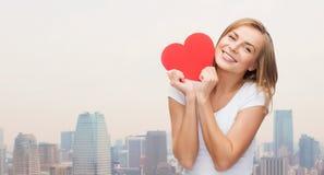 Χαμογελώντας γυναίκα στην άσπρη μπλούζα που κρατά την κόκκινη καρδιά Στοκ Εικόνα