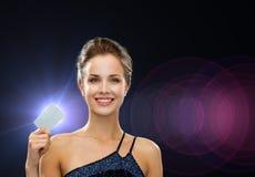 Χαμογελώντας γυναίκα στην πιστωτική κάρτα εκμετάλλευσης φορεμάτων βραδιού Στοκ φωτογραφία με δικαίωμα ελεύθερης χρήσης