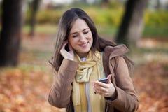 Χαμογελώντας γυναίκα στη μουσική ακούσματος πάρκων MP3 Στοκ φωτογραφία με δικαίωμα ελεύθερης χρήσης