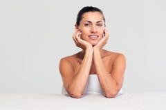 Χαμογελώντας γυναίκα στη συνεδρίαση πετσετών στον πίνακα Στοκ Εικόνες