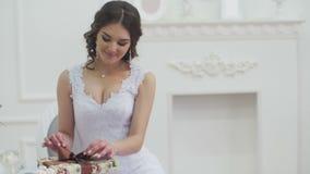 Χαμογελώντας γυναίκα στο άσπρο κιβώτιο δώρων εκμετάλλευσης φορεμάτων με την κορδέλλα απόθεμα βίντεο